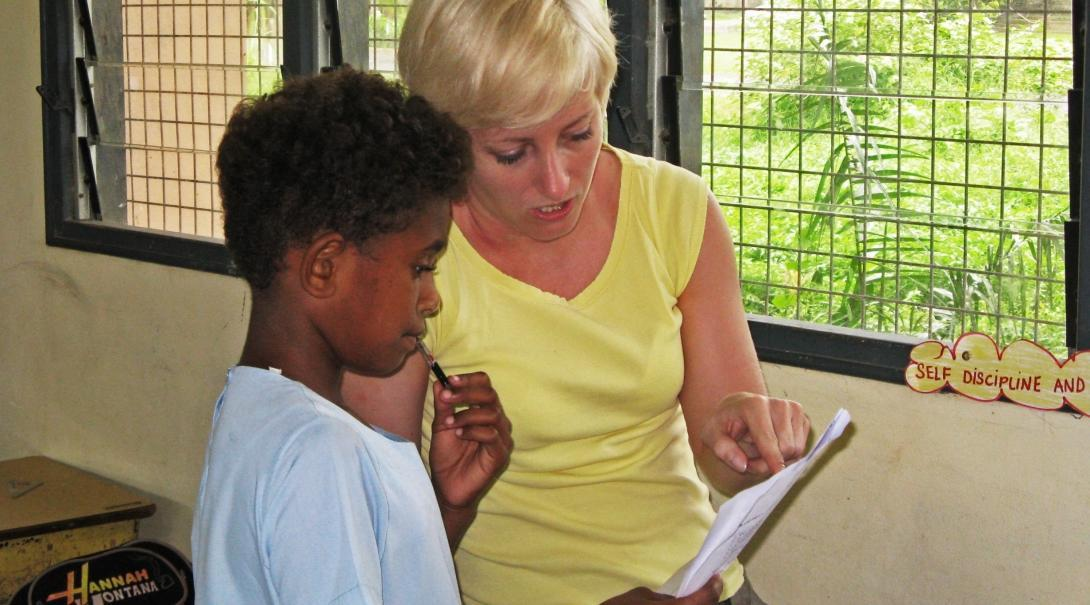 A volunteer gains teaching work experience in Fiji while helping a young boy with his schoolwork